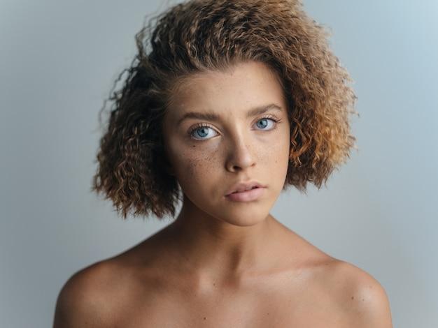 Schöner frauenporträtlichthintergrund entblößte schultern lockiges haar. hochwertiges foto