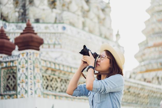 Schöner frauentourist held kamera, um die erinnerungen einzufangen. wat arun tempel in thailand.