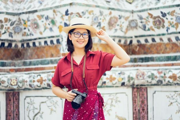 Schöner frauentourist held kamera, um die erinnerungen einzufangen. wat arun tempel