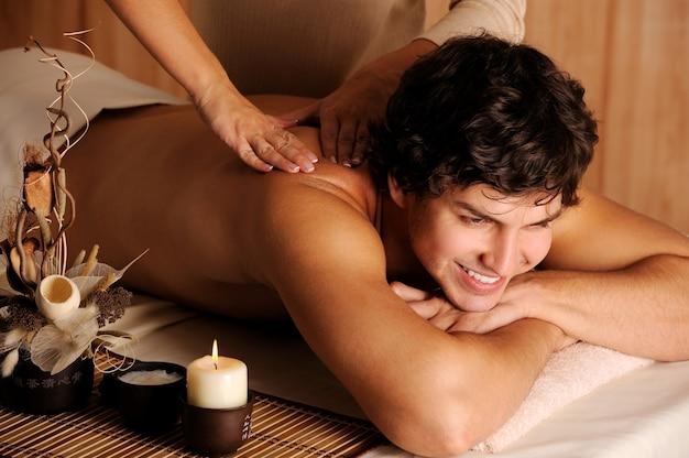 Schöner fröhlicher kerl, der massage und entspannung bekommt - zurückhaltendes licht