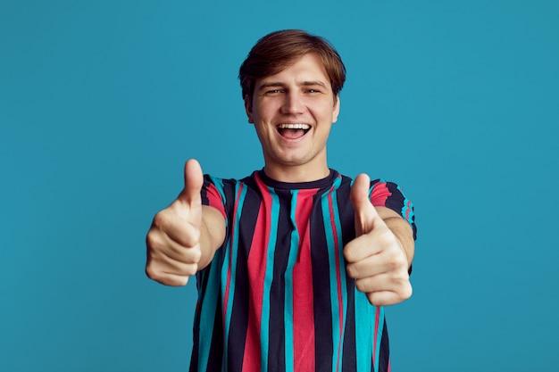Schöner fröhlicher mann, der mit beiden händen lächelt und daumen hoch zeigt