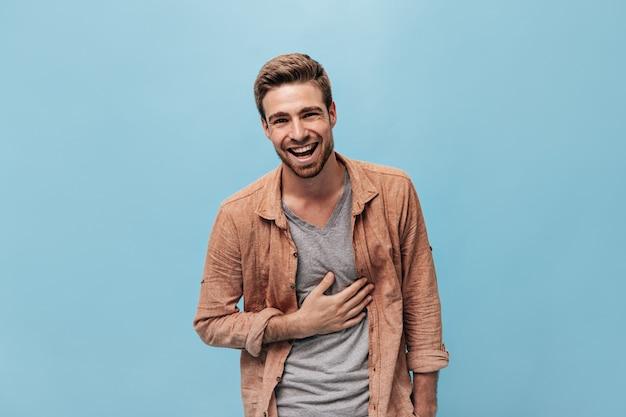 Schöner fröhlicher mann in modernem t-shirt und beigem coolem hemd, der lacht und auf die isolierte blaue wand schaut