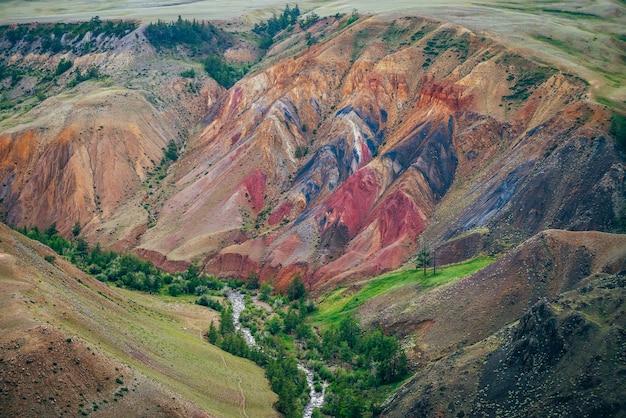 Schöner gebirgsfluss und grüne bäume im tal zwischen mehrfarbigen lehmhügeln. malerische landschaft mit gebirgsbach in buntem canyon und lebendigen mehrfarbigen bergen. malerische berglandschaft