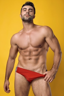 Schöner gebräunter muskulöser mann, der eine rote badebekleidung auf einer gelben wand trägt