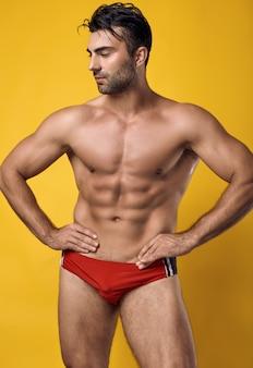 Schöner gebräunter muskulöser mann, der eine rote badebekleidung trägt