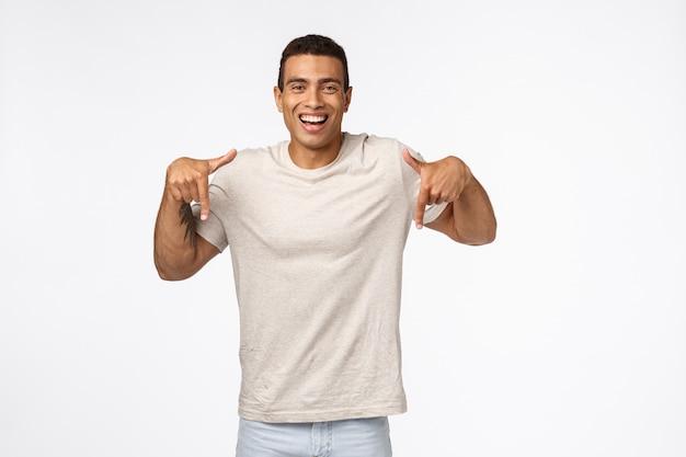 Schöner gebräunter starker mann muscline im zufälligen t-shirt, unten zeigend