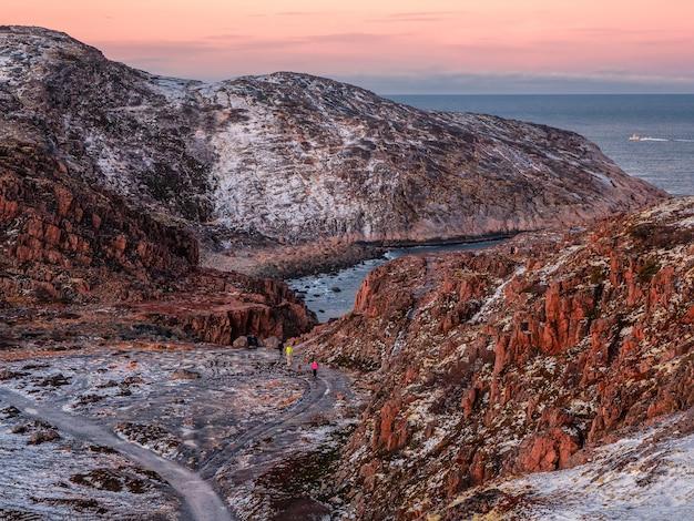 Schöner gefrorener felsiger hang des berges. touristengruppe in der schlucht zwischen den felsen. malerische arktische landschaft in teriberka. bunte berglandschaft. russland.