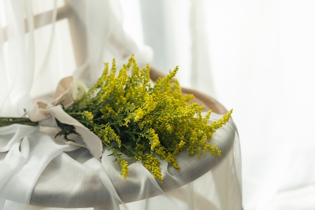 Schöner gelber blumenblumenstrauß mit weißem leinenstoff auf holzstuhl