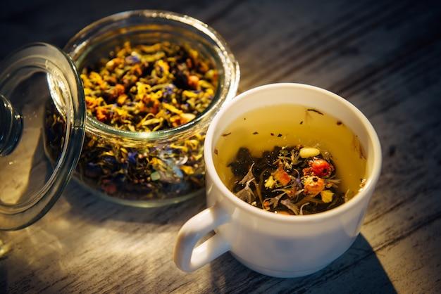 Schöner gemischter tee aus kräutern, beeren und nüssen in weißem becher und transparenter glasschale auf vintage-holzhintergrund, nahaufnahme. tee aufbrühen im abendlicht. gesunder lebensstil, entgiftung.