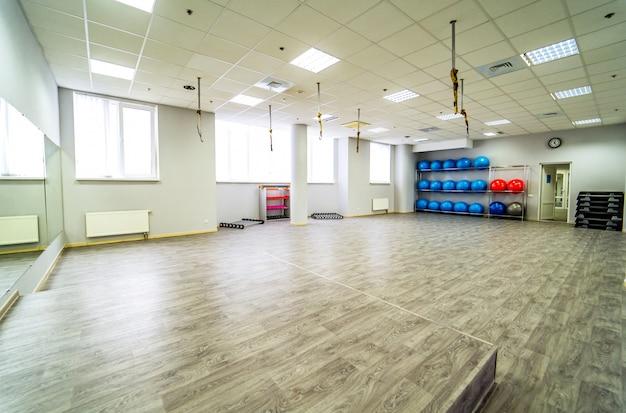 Schöner geräumiger fitnessraum für fitnesstraining mit sportgeräten.