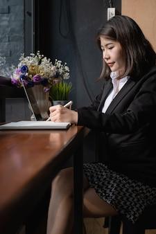 Schöner geschäftsfraubehälter und anwendung des digitalen tablettengeräts.