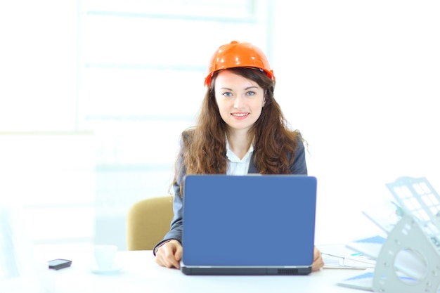 Schöner geschäftsfrauingenieur, der an einem laptop im büro arbeitet.