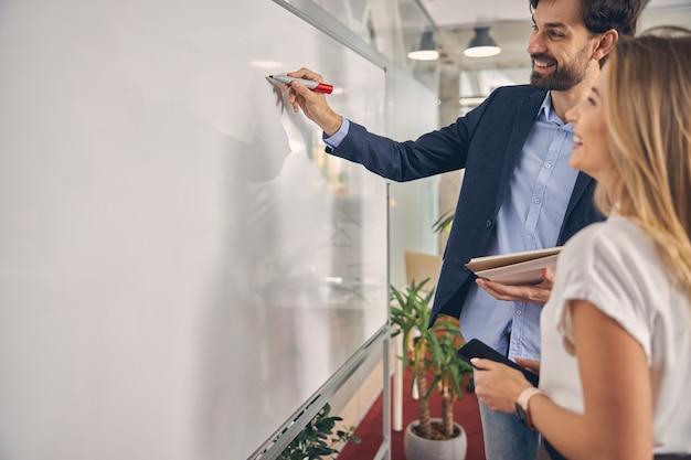 Schöner geschäftsmann, der auf whiteboard schreibt und lächelt, während seine kollegin smartphone hält holding