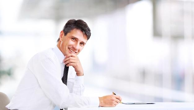 Schöner geschäftsmann, der im büro lächelt