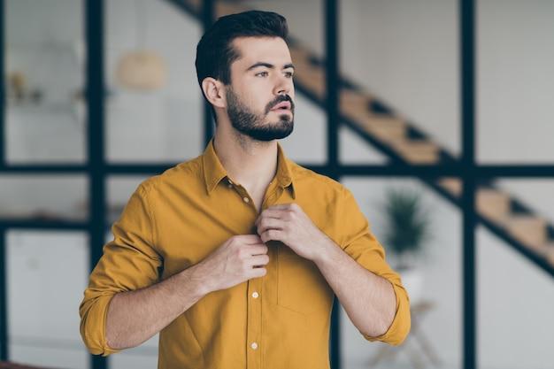 Schöner geschäftsmann der nahaufnahme, der das knöpfen des gelben hemdes vorbereitet, das im bürogebäude der stilvollen innenwohnungen innen steht