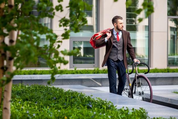 Schöner geschäftsmann und sein fahrrad