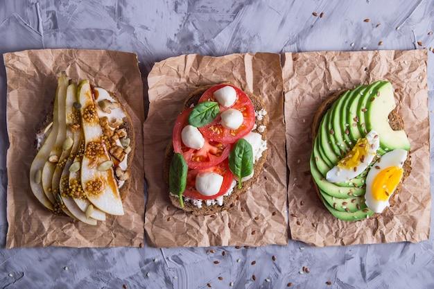 Schöner gesunder snack - sandwiches mit roggenbrot mit avocado und ei, mozzarella