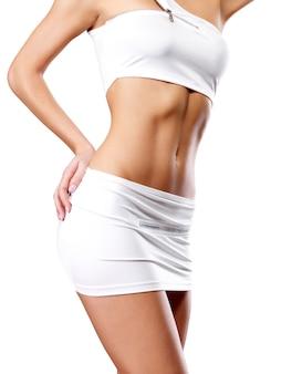 Schöner gesunder weiblicher körper in der weißen sportkleidung