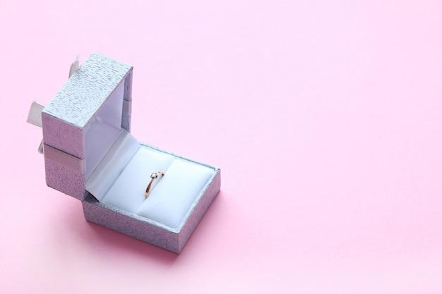 Schöner glänzender goldverlobungsring mit edelsteindiamant im grauen kasten auf rosa hintergrund.