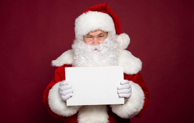 Schöner glücklicher aufgeregter weihnachtsmann posiert und zeigt weiße leere tafel in händen