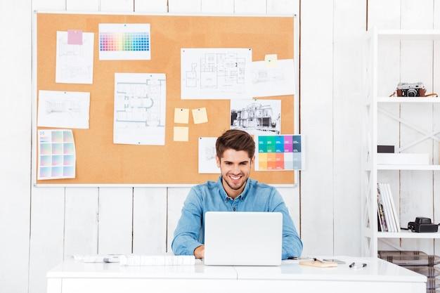 Schöner glücklicher geschäftsmann, der mit laptop arbeitet, während er im büro sitzt