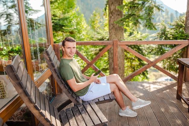Schöner glücklicher junger mann in den bergen im nebel
