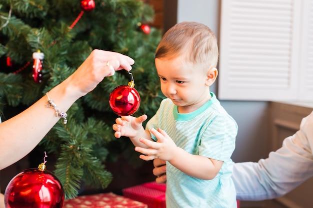 Schöner glücklicher kleiner junge mit weihnachtsball