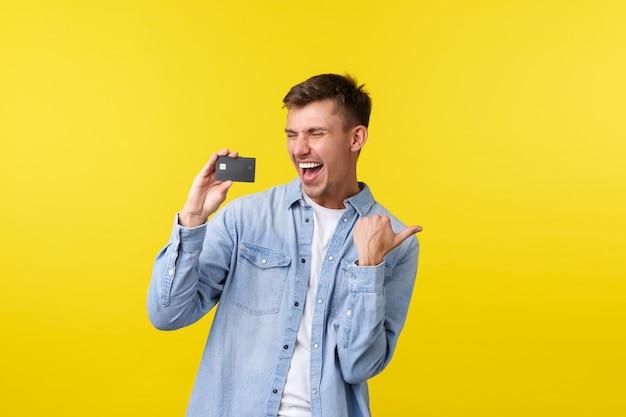 Schöner glücklicher mann, der den sieg feiert und triumphiert. kerl, der kreditkarte zeigt und vor erstaunen und freude ja schreit, erhält boni, zusätzliches cashback, steht auf gelbem hintergrund.