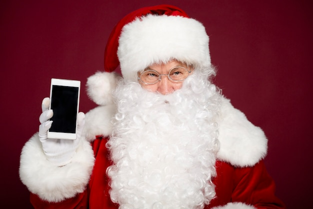 Schöner glücklicher weihnachtsmann zeigt den weißen leeren bildschirm eines smartphones