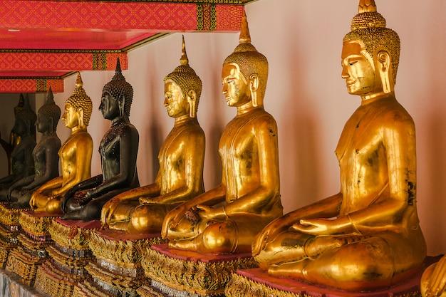 Schöner goldener buddha auf dem sockel einige weiße wände