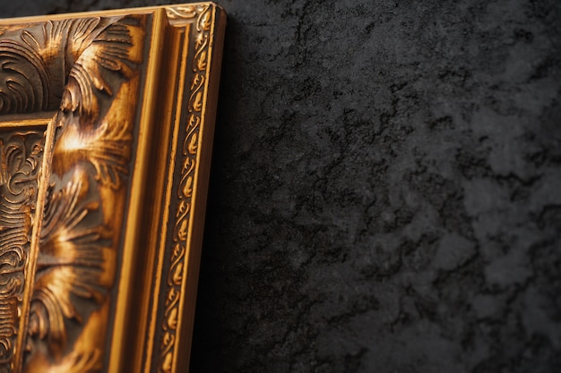 Schöner goldener rahmen auf schwarzer wand mit musternahaufnahme