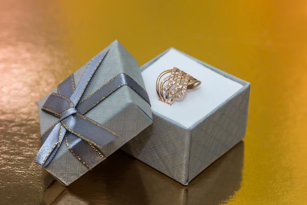 Schöner goldener schmuck in der geschenkbox auf goldenem hintergrund