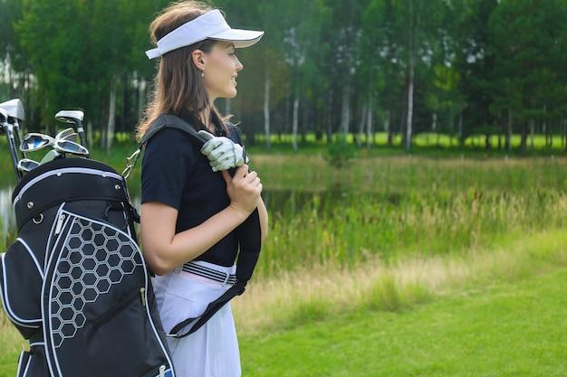 Schöner golfspieler, der eine golftasche trägt und lächelt.