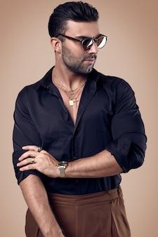 Schöner grober gebräunter hippie-mann in einem schwarzen hemd und in den gläsern