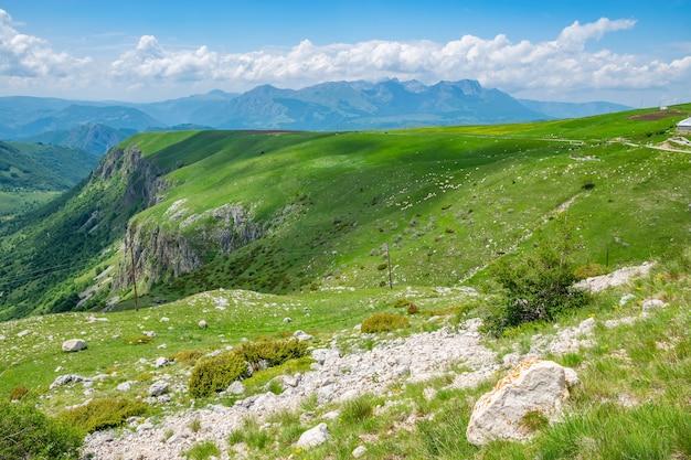 Schöner grüner grasberg mit weißen wolken am blauen himmel