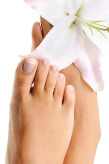 Schöner gut gepflegter weiblicher fuß mit der französischen pediküre und der lilienblume darauf