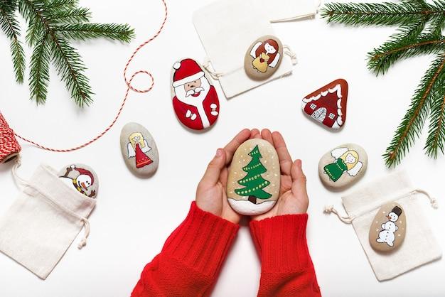 Schöner handgemalter stein mit weihnachtsbaumgriff durch hände, draufsicht