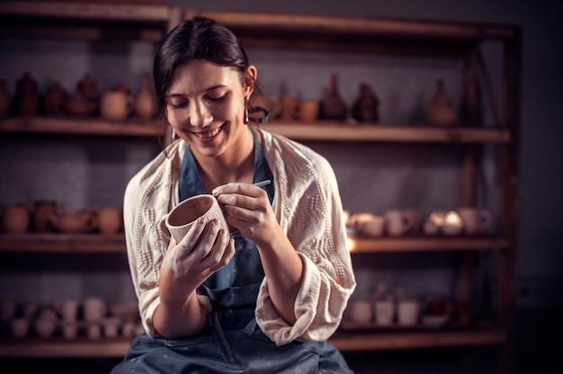 Schöner handwerker, der eine tonvase auf einer töpferscheibe formt. handarbeit.