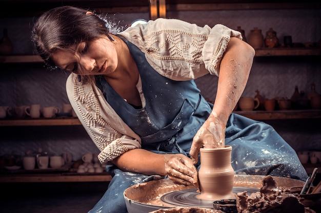 Schöner handwerker meister posiert beim herstellen von steingut. handarbeit.
