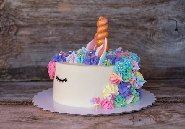 Schöner hausgemachter kuchen in form eines einhorns mit cremefarbenen blumen auf einem holztisch