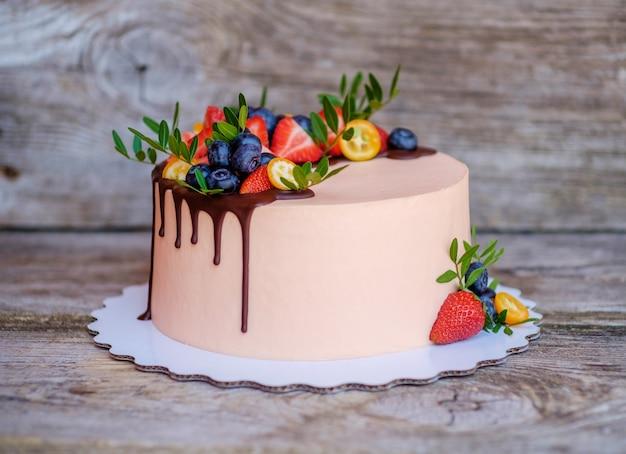 Schöner hausgemachter kuchen mit frischkäse-zuckerguss, erdbeeren und blaubeeren auf einem holztisch