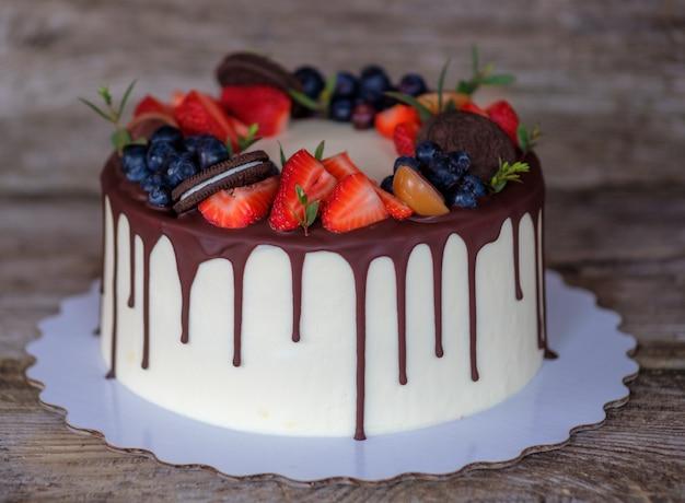 Schöner hausgemachter kuchen mit käsecreme, erdbeeren und blaubeeren