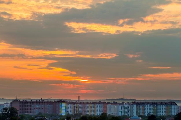 Schöner heller orange himmel bei sonnenuntergang über hohem wohnhaus, arbeitsturmkräne und hausdächer unter grünen bäumen auf entferntem gebirgshintergrund. bau- und immobilienkonzept.