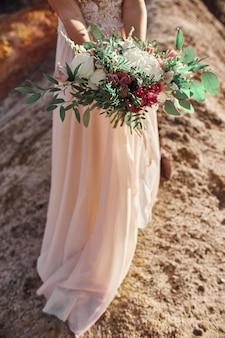 Schöner herbstblumenstrauß in den händen von frauen. das mädchen mit dem hochzeitsstrauß in den händen