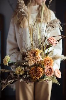 Schöner herbstblumenstrauß von mischblumen mit trockenen winden in den händen einer frau.