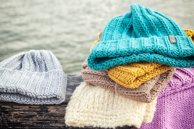 Schöner hintergrund, der winter blau und gelb viel hut strickt. häkelnadel handgefertigt. nahaufnahme von strickmützen in blau, gelb, rosa und weiß