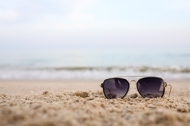 Schöner hintergrund des türkisfarbenen meeres mit sonnenbrille am sandstrand. das konzept des ruheurlaubs. breite horizontale bunte tapete mit selektivem fokus und kopienraum