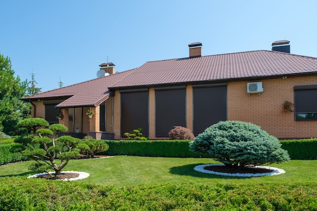 Schöner hinterhofgarten mit schön geschnittenen bonsai, büschen und bäumen vor der villa im europäischen stil. landschaftsdesign. foto in hoher qualität