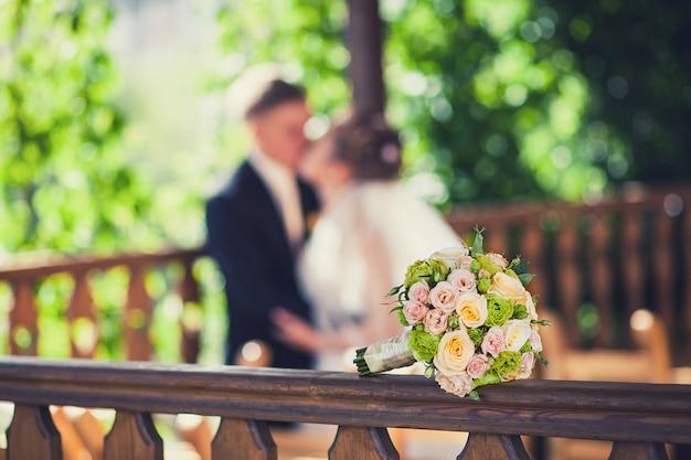 Schöner hochzeitsblumenstrauß auf dem hintergrund des küssens der braut und des bräutigams