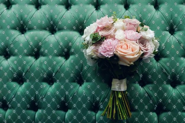 Schöner hochzeitsblumenstrauß auf einem luxuriösen velourhintergrund, gebunden mit einem satinband.
